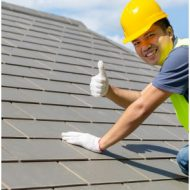a tradesman giving a thumbs up on a roof of a residential build